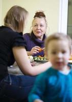 Großmutter und Mutter unterhalten sich, während das Kind spielt