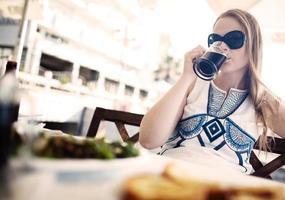 Frau genießt ein dunkles Bier mit ihrer Mahlzeit foto