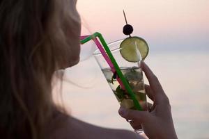 Frau trinkt einen Mojito-Cocktail foto