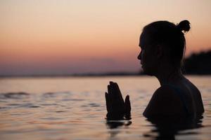 Silhouette einer Person im Gebet im Wasser foto