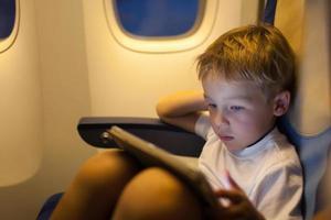 Junge sitzt in einem Flugzeug mit einer Tablette foto