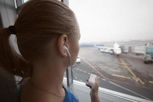 Frau in den Kopfhörern, die Flughafen betrachten foto