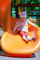kleines Mädchen, das Spaß auf einer Rutsche hat foto