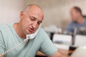 Geschäftsmann, der an einem Telefon in einem Büro spricht