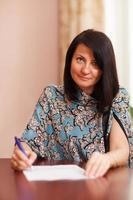 Frau, die an einem Schreibtisch schreibt foto