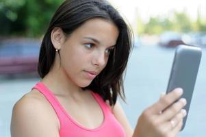 Mädchen mit einer Tablette draußen foto