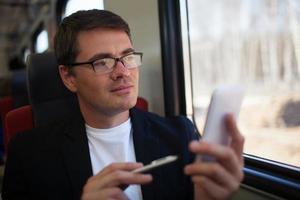 Mann mit einem Telefon in einem Zug foto