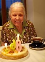 Großmutter bläst Geburtstagskerzen aus foto