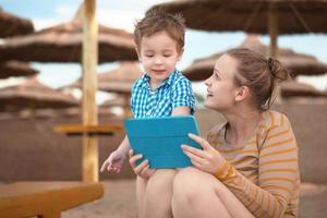 Junge und Mutter mit einer Tablette foto