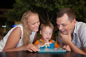 Familie mit einer Tablette draußen foto