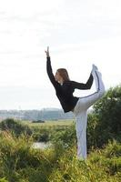 Frau, die draußen Yoga praktiziert foto