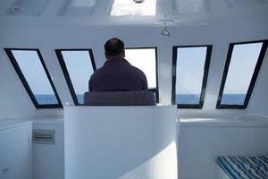 Mann, der ein Boot navigiert foto