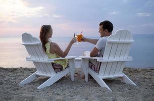 romantisches Paar, das den Sonnenuntergang anstößt foto