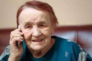 ältere Frau, die auf einem Mobiltelefon spricht foto