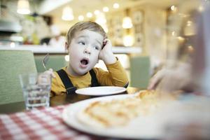 Junge, der an einem Restauranttisch gähnt foto