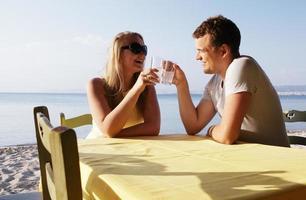 junges Paar, das Getränke am Meer genießt foto