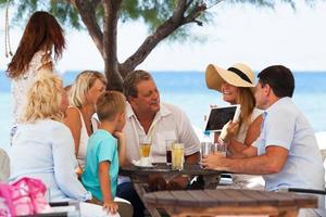 Familie, die Foto auf einer Tablette in einem Straßencafé betrachtet