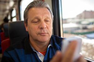 Mann mit Handy während einer Zugfahrt foto