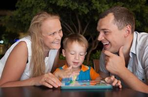 glückliche Familie mit einem Tablet foto