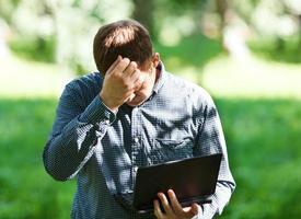 frustrierter Mann draußen mit einem Laptop foto