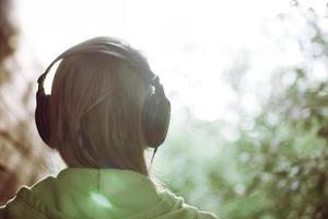 Frau in Kopfhörern gegen helles Sonnenlicht foto