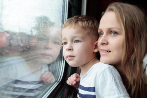 Mutter und Sohn schauen aus einem Zugfenster foto