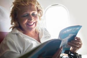 reife Frau, die eine Zeitschrift in einem Flugzeug liest foto