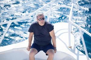 Mann sitzt auf dem Bug eines Bootes foto