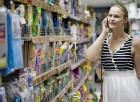 Frau, die auf ihrem Handy beim Einkaufen plaudert foto