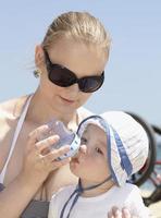 Mutter füttert ihren Sohn am Strand foto