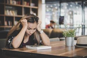 Geschäftsfrau, die sich gestresst fühlt, während sie im Café sitzt foto