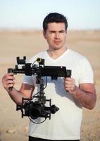 Videofilmer mit Steady-Cam-Ausrüstung am Strand