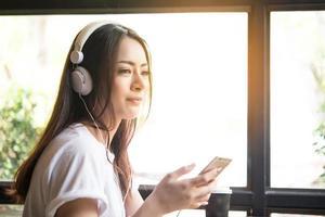 junge Frau, die Musik auf Kopfhörern mit Fensterbankhintergrund hört