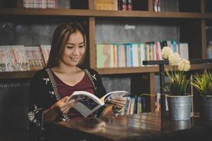 glückliche Geschäftsfrau, die Buch liest, während sie im Café entspannt.