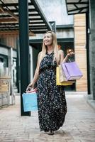 Porträt einer jungen glücklichen Frau mit Einkaufstüten, die auf der Straße gehen