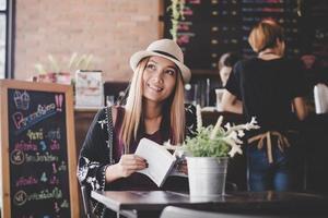glückliche Geschäftsfrau, die Buch liest, während sie im Café entspannt
