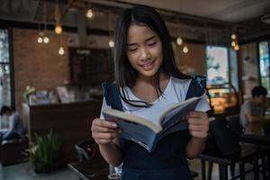junge Frau, die Buch liest, das drinnen im städtischen Café sitzt