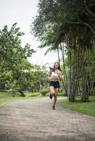 junge sportliche Frau, die am Park läuft