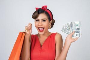 schöne asiatische Frau, die farbige Einkaufstaschen und Geld hält