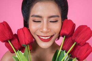 Porträt einer schönen Frau mit Strauß roter Tulpenblumen foto