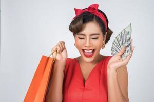 schöne asiatische Frau, die farbige Einkaufstaschen und Geld hält foto
