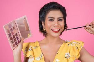Porträt einer Frau mit Make-up und Kosmetikpinsel foto