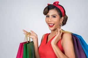 schöne asiatische Frau, die farbige Einkaufstaschen hält