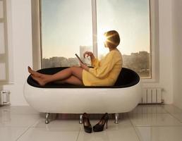 Frau, die in der Nähe eines Fensters zur goldenen Stunde entspannt foto