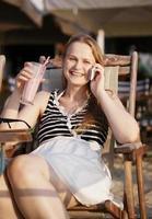 Frau, die in einem Liegestuhl in der Sonne entspannt foto