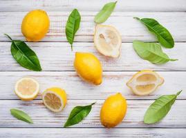 Zitronen und Blätter auf einem rustikalen hölzernen Hintergrund foto