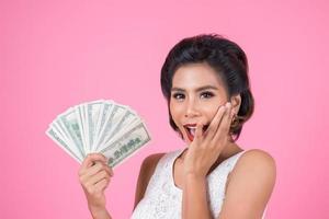 glückliche schöne Frau, die Dollars hält