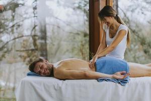 schöner junger Mann, der während der Wintersaison im Spa-Salon liegt und Rückenmassage hat foto