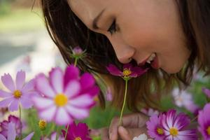 Nahaufnahme der fröhlichen Frau, die Kosmosblumen in einem Garten riecht foto