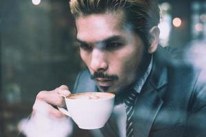 Geschäftsmann, der Kaffee im Stadtcafé während der Mittagszeit trinkt foto